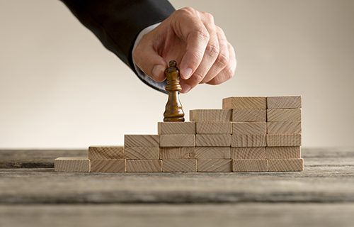 Business success and promotion concept with a businessman moving the queen piece up a series of steps formed by building blocks.