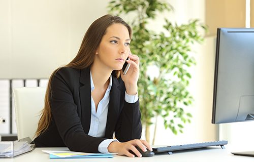 Concentrated businesswoman talking on the phone and checking information in a desktop computer