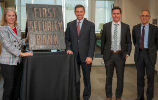 The Youngs and YESCO present Lisa Eccles with the First Security Bank sign